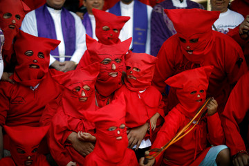 Men and children dressed as demons pose for pictures prior to the ceremony known as Los Talciguines, as part of religious activities to mark the start of the Holy Week in Texistepeque