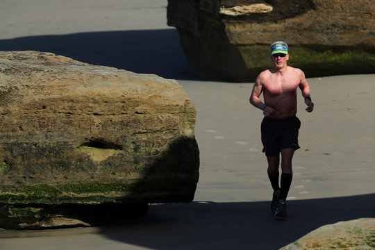 A man works out along the ocean as he goes for a morning run in Solana Beach, California