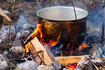 Iron pot with food on a burning fire. Food in a metal cauldron is cooked on fire. Cooking food in nature. Eating out for a picnic on a summer sunny day in the forest.