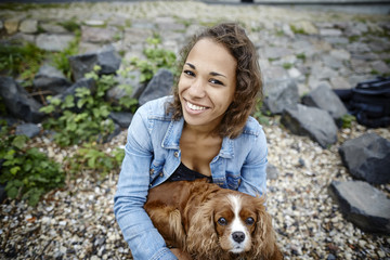 Smiling young woman with dog outdoors