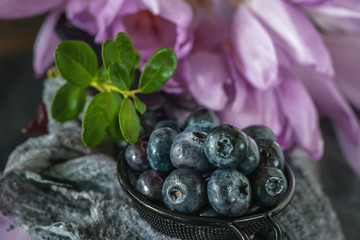 Ripe blueberry and blueberry in a metal Cup against the background of delicate flowers timeless. Close up.