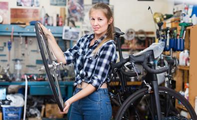 Young girl master cheking wheel of bicycle