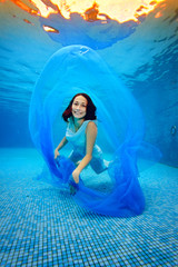 The girl in the dress posing underwater at the bottom of the pool, playing with a blue cloth, looking at the camera and smiling at the background of bright light. Portrait