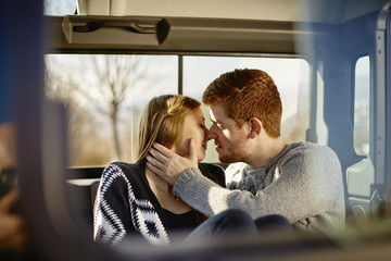 Young couple kissing inside car