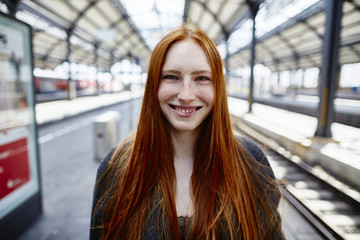 Portrait of smiling redheaded young woman on station platform