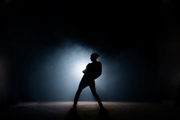young male dancing on dark stage. first performance. body bent. street dance Wall mural