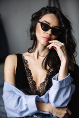 portrait of a beautiful brunette in sunglasses, blue shirt, blue jeans and interior in room