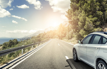 A white car rushing along a high-speed highway in the sun. Fototapete