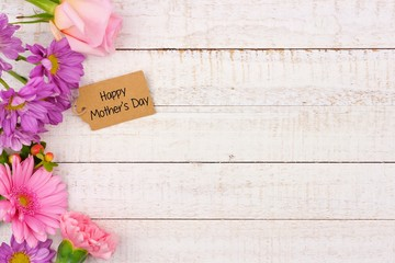 Side border of flowers with Mothers Day gift tag against a rustic white wood background