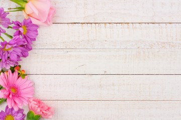 Side border of pink and purple flowers with rose, carnation and daisies against a white wood background. Copy space.