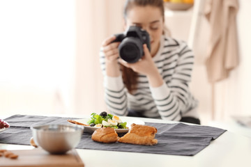 Young woman with professional camera taking still life pictures. Focus on food