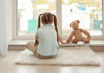 Lonely little girl with teddy bear sitting near window. Autism concept