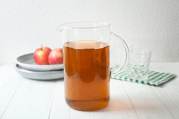 Jug with fresh apple juice on wooden table