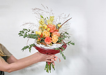 Young florist holding beautiful bouquet on white wall background