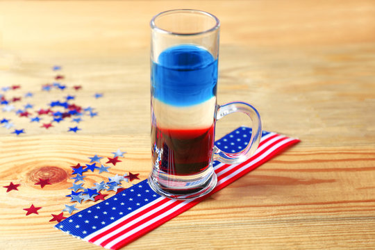 Layered cocktail in colors of American flag on wooden table