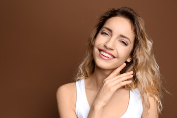 Young woman with beautiful smile on color background. Teeth whitening