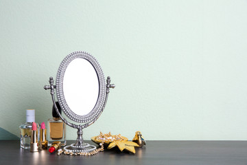 Stylish mirror, makeup products and accessories on table near light wall