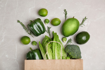 Paper package with green vegetables and fruits on grey background, top view
