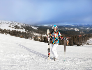 Woman on ski piste at snowy resort. Winter vacation