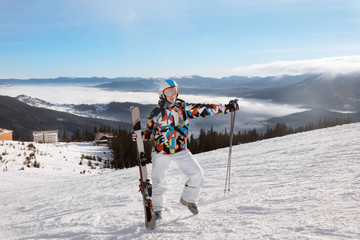 Woman on ski piste at snowy resort. Winter vacation