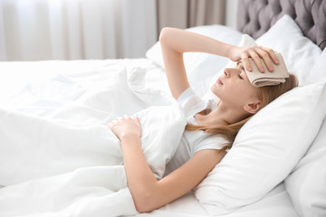 Teenage girl suffering from headache while lying in bed at home
