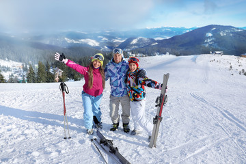 Happy friends on ski piste at snowy resort. Winter vacation