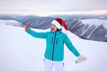 Happy woman taking selfie at snowy resort. Winter vacation