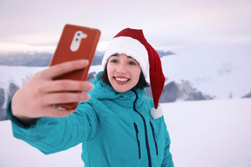 Happy woman taking selfie at snowy resort. Winter vacation
