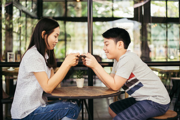 Asian woman with asian boy play game in smartphone in cafe