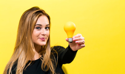 Wall Mural - Young woman holding a light bulb on a yellow background