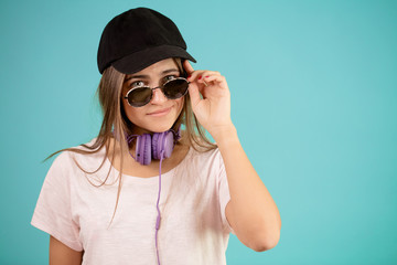 young female with sunglasses and headphones is wearing black cap isolated on the blue background. sportswoman