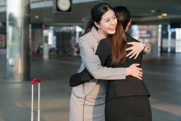 Businesswomen hugging deeply.