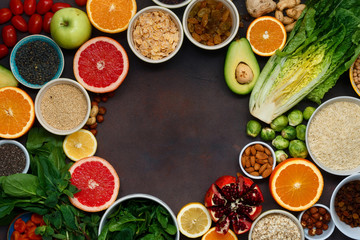 Clean eating concept. Frame of vegetarian healthy food - different vegetables and fruits, superfood, seeds, cereal, leaf vegetable on dark background, top view. Flat lay