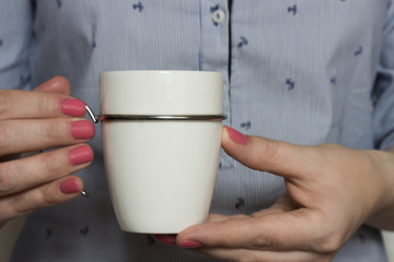 White ceramic mug on the forefront of shirt, close-up. Female hands with pink manicure hold a mug. Space for text