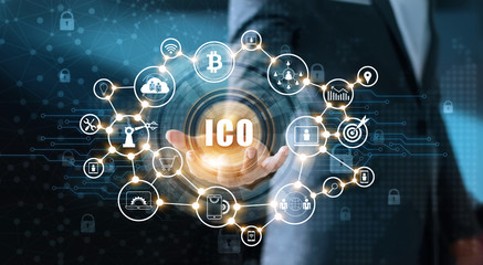 Businessman holding icon with ICO or Initial Coin Offering on interface virtual screen. Digital currency network concept
