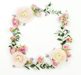 Flowers background. Wreath frame made of  pale pink roses and ranunculus  flowers and eucalyptus branches on a white background. Flat lay. top view. copy space