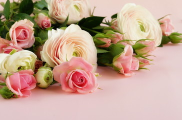 beautiful bouquet of gently pink roses and ranunculus on a pale pink background. close up. top view.copy space
