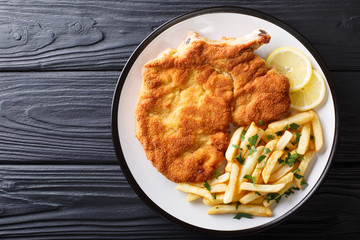 Traditional Italian veal Milanese with lemon and French fries close-up. horizontal top view