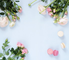 Holiday flowers background. Beautiful bouquets  of pale pink roses and ranunculus flowers and macaroons cakes on pale blue background. Top view. Copy space,. Flat lay