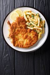 Traditional Italian veal Milanese with lemon and French fries close-up. Vertical top view