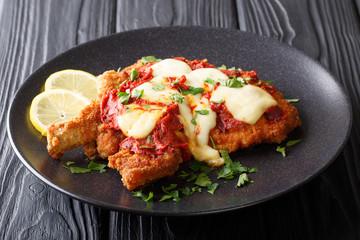 Delicious veal cutlet with mozzarella cheese, lemon and tomato sauce (milanesa napolitana) close-up. horizontal