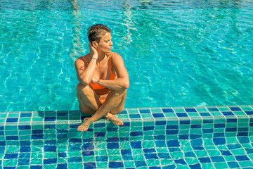 Beautiful tanned woman in swimwear relaxing in swimming pool