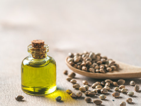 Hemp seeds and hemp oil on brown wooden table. Hemp seeds in wooden spoon and hemp essential oil in small glass bottle. Copy space for text
