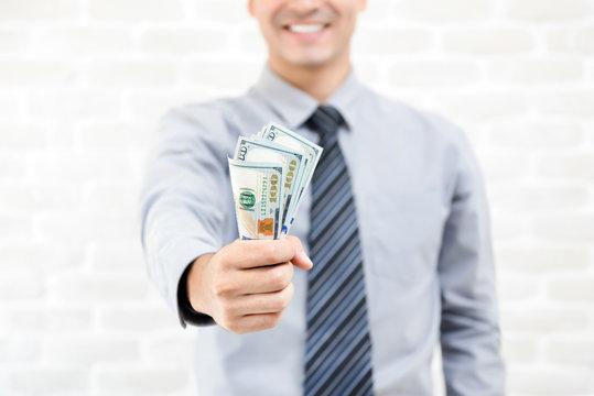 Money, United States dollar banknotes, in businessman hand