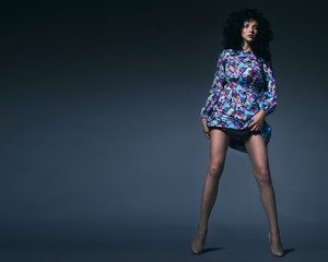 beautiful skinny model girl with tall straight legs in colorful short dress with flowers. Studio shot.