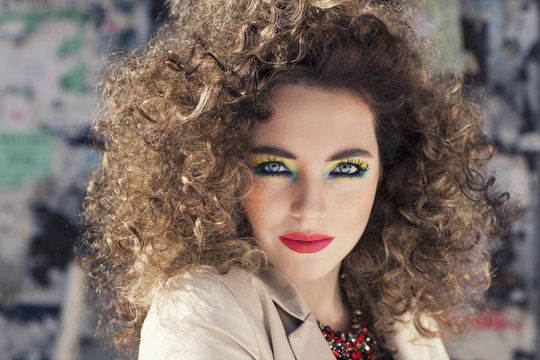 Young beautiful model with bright make-up standing on the street  girl with expressive make-up and curly hair.