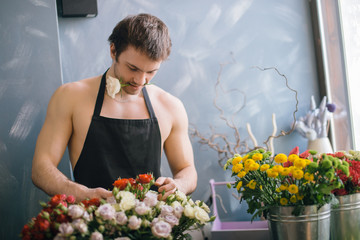 Caucasian young shop assistant selecting best flowers for sale