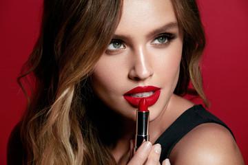 Red Lips. Beautiful Woman With Beauty Makeup Holding Lipstick.