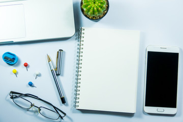 Top view of laptop, blank notebook, paper clips  and smart phone with white background and copy space.