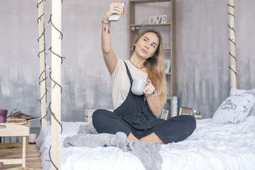 Stylish caucasian woman in casual hipster outfit sitting on a bed in her morning, making selfie. Space for text